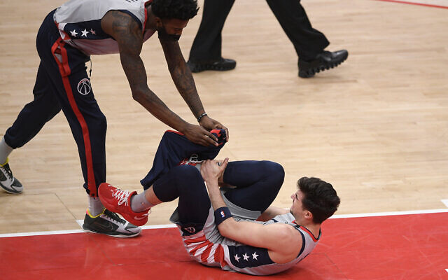 Washington Wizards forward Deni Avdija, bottom, reacts after he was injured during the first half of an NBA basketball game against the Golden State Warriors, April 21, 2021, in Washington. Also seen is Wizards center Jordan Bell (7). (AP Photo/Nick Wass)