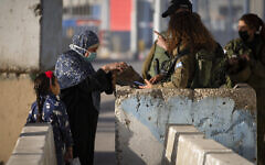 Israeli soldiers check a Palestinian woman as she wait to cross the Qalandiya checkpoint between the West Bank city of Ramallah and Jerusalem, to attend the second Friday prayers in the al-Aqsa mosque during the Muslim holy month of Ramadan on April 23, 2021. (AP/Majdi Mohammed)