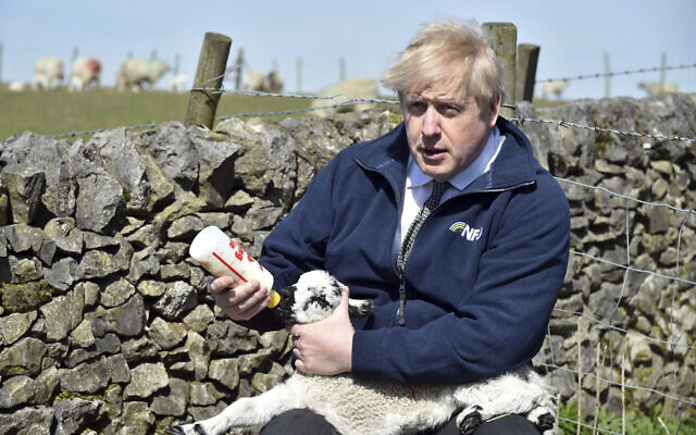 Britain's Prime Minister Boris Johnson feeds a lamb at Moor Farm in Stoney Middleton, England on April 23, 2021. (AP/Rui Vieira, Pool)