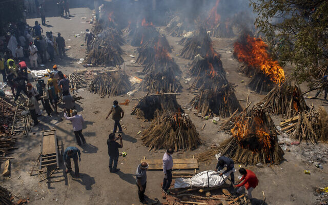 Multiple funeral pyres of victims of COVID-19 burn at a ground that has been converted into a crematorium for mass cremation in New Delhi, India, April 24, 2021. (Altaf Qadri/AP)
