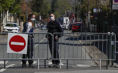 French police officers block the access next to the police station where a police official was stabbed to death Friday in Rambouillet, south west of Paris, Saturday, April 24, 2021. (AP Photo/Michel Euler)