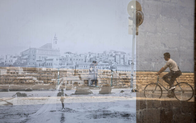 A man riding his bicycle is reflected on an old picture of Jaffa displayed in a window, in the Jaffa neighborhood of Tel Aviv, Israel, April 21, 2021. (AP Photo/Sebastian Scheiner)