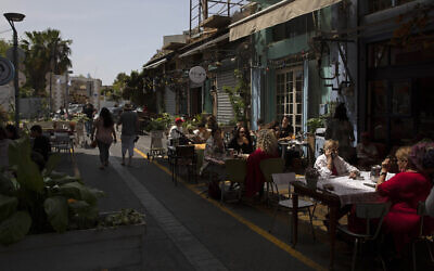 People sit in a restaurant in the Jaffa section of Tel Aviv, on April 21, 2021. (AP Photo/Sebastian Scheiner)