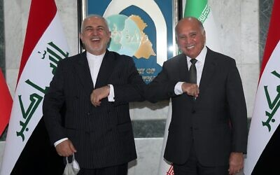 Iraqi Foreign Minister Fouad Hussein, right, meets with visiting Iranian counterpart Mohammad Javad Zarif in Baghdad, Iraq, April 26, 2021. (AP Photo/Khalid Mohammed)
