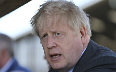 Britain's Prime Minister Boris Johnson visits a farm as he campaigns on behalf of the Conservative Party for local elections, at Moreton farm near Wrexham, north Wales, Monday, April 26, 2021. (Paul Ellis/Pool Photo via AP)