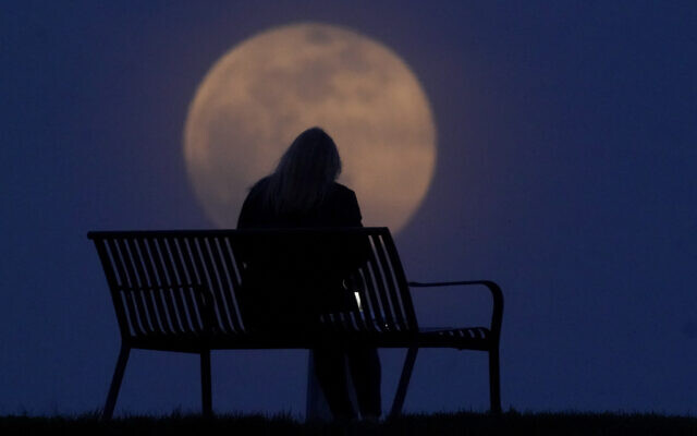 A woman sits at a park as the moon rises, Monday, April 26, 2021, in New Albany, Ind.  (AP Photo/Charlie Riedel)