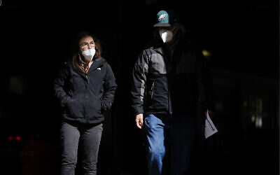 In this Wednesday, March 3, 2021 file photo, people wearing face masks as a precaution against the coronavirus walk through a shaft of light on a street in Philadelphia. (AP/Matt Rourke)