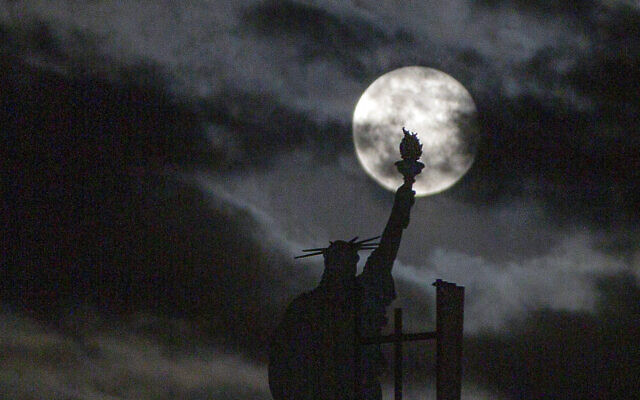 The moon rises over a replica of Statue of Liberty in Kosovo capital Pristina on Tuesday, April 27, 2021. This moon is a supermoon, meaning it appears larger than an average full moon because it is nearer the closest point of its orbit to Earth. (AP Photo/Visar Kryeziu)