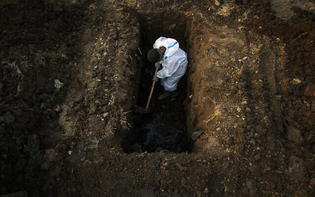 A man in protective suit digs earth to bury the body of a person who died of COVID-19 in Gauhati, India, April 25, 2021. (AP Photo/Anupam Nath, File)