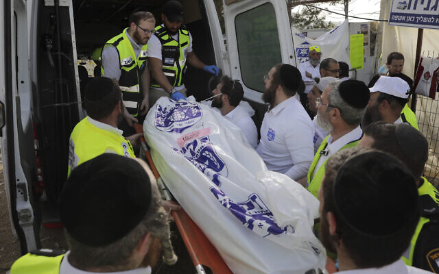 Israeli security officials and rescuers carry the body of a victim who died during a Lag B'Omer celebration at Mt. Meron in northern Israel, April 30, 2021 (AP Photo/Sebastian Scheiner)