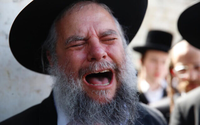 A man weeps at the funeral of Rabbi Eliezer Goldberg, who died during Lag BaOmer celebrations at Mt. Meron in northern Israel, in Jerusalem on Friday, April 30, 2021.(AP Photo/Ariel Schalit)