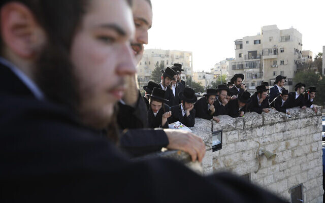 Ultra-Orthodox men watch the funeral of Shraga Gestetner, a Canadian singer who died during Lag B'Omer celebrations at Mt. Meron in northern Israel, in Jerusalem on Friday, April 30, 2021. (AP Photo/Ariel Schalit)
