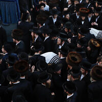 Ultra-Orthodox men carry the bodies of Moshe Englander, 14, and his brother, Yehoshua, 9, who died during Lag B'Omer celebrations at Mt. Meron in northern Israel, in Jerusalem on Friday, April 30, 2021. (AP Photo/Ariel Schalit)