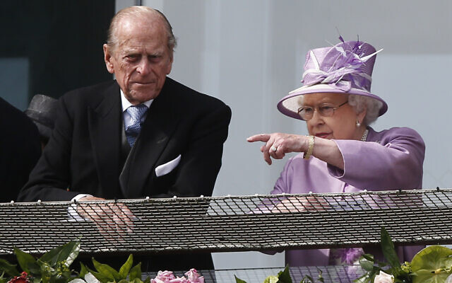 Britain's Queen Elizabeth II points out something to Prince Philip as they watch the Epsom Derby from the balcony at Epsom racecourse, England, June 7, 2014. (AP Photo/Sang Tan)