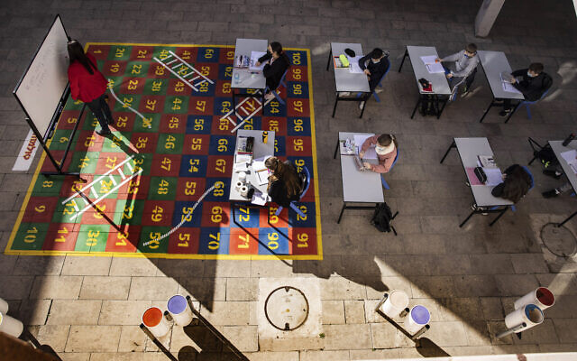 Students take part in a lesson in their makeshift outdoor classroom in the coastal city of Ashkelon, February 11, 2021. (AP Photo/Tsafrir Abayov)