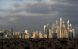 The sunrise reflects on city skylines at the Marina and Jumeirah Lake Towers districts in Dubai, United Arab Emirates, Feb. 27, 2021. (AP Photo/Kamran Jebreili)
