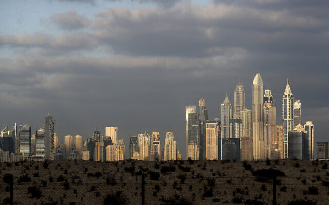 The sunrise reflects on city skylines at the Marina and Jumeirah Lake Towers districts in Dubai, United Arab Emirates, Feb. 27, 2021. (AP Photo/Kamran Jebreili)