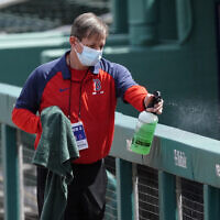A Boston Red Sox staff member disinfects the railing in front of the visitor's dugout before a spring training baseball game between the Atlanta Braves and Boston Red Sox, March 10, 2021, in Fort Myers, Florida. (AP/John Bazemore)