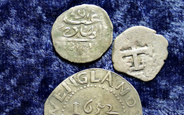 A 17th century Arabian silver coin, top, that research shows was struck in 1693 in Yemen, rests near an Oak Tree Shilling minted in 1652 by the Massachusetts Bay Colony, below, and a Spanish half real coin from 1727, right, on a table, in Warwick, Rhode Island, March 11, 2021 (AP Photo/Steven Senne)