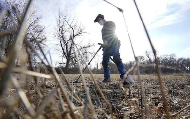 Amateur historian Jim Bailey uses a metal detector to scan for Colonial-era artifacts in a field, March 11, 2021, in Warwick (AP Photo/Steven Senne)