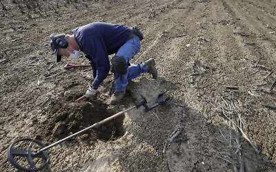 Metal detectorist Jim Bailey scans dirt for Colonial-era artifacts in a field, March 11, 2021, in Warwick (AP Photo/Steven Senne)