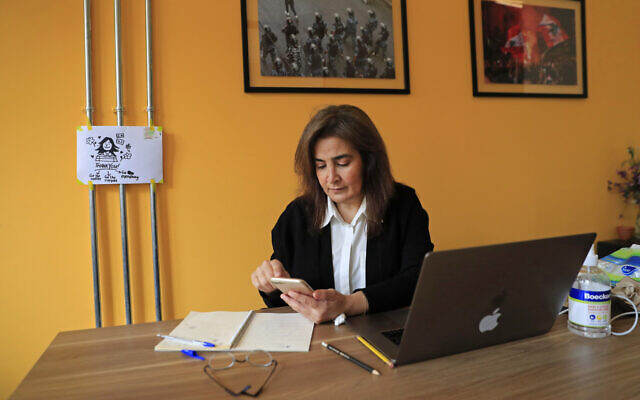 Diana Moukalled, a Lebanese journalist who closely follows social media checks the Clubhouse application, at her office in Beirut, Lebanon, April 7, 2021 (AP Photo/Hussein Malla)
