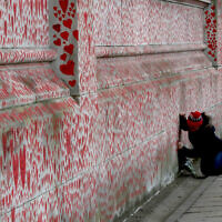 People paint red hearts marking the completion of the approximately 150,000 hearts being painted onto the National Covid Memorial Wall to commemorate all those who have died of coronavirus, on the Thames Embankment opposite the Houses of Parliament in London, April 8, 2021. (Frank Augstein/AP)