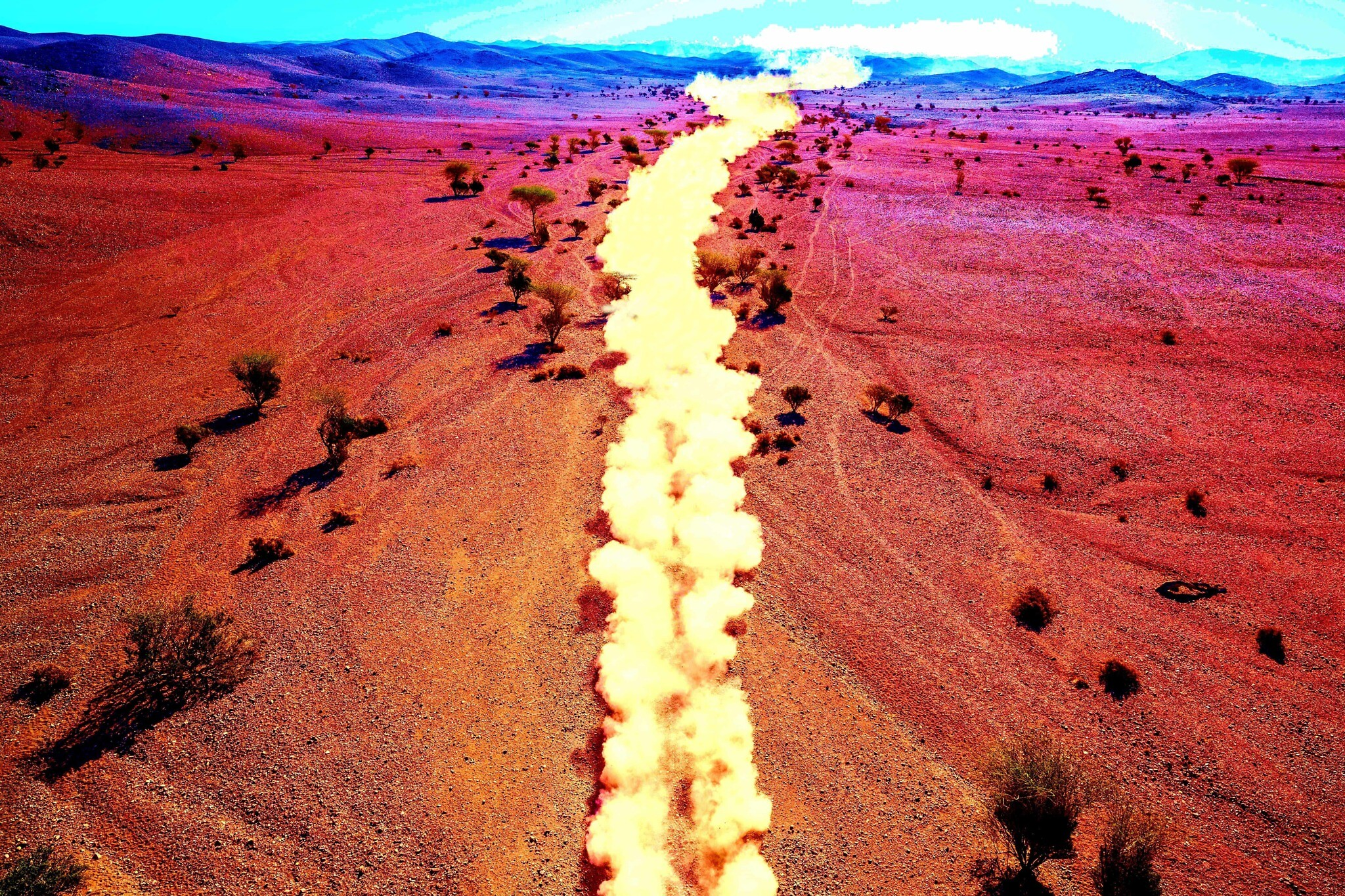 A color-adjusted photo of a race car kicking up a trail of dust during stage two of the Dakar Rally between Al Wajh and Neom, Saudi Arabia, on Monday, January 6, 2020. (Photo: AP/Bernat Armangue; Illustration: Joshua Davidovich/Times of Israel)