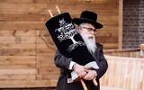 Ukrainian Chief Rabbi Yaakov Dov Bleich holds a Torah scroll during the opening ceremony of the Babyn Yar synagogue in Kyiv, April 7, 2021. (Babyn Yar Holocaust Memorial Center)
