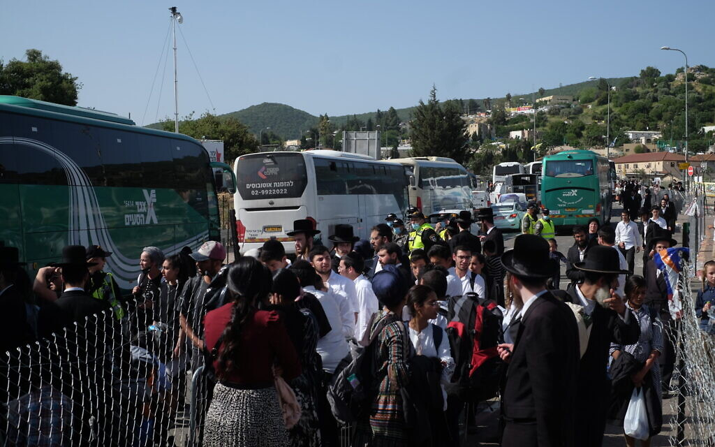 Masses of people try to get on buses to leave Mount Meron following a deadly crush on April 30, 2021. (Judah Ari Gross/Times of Israel)