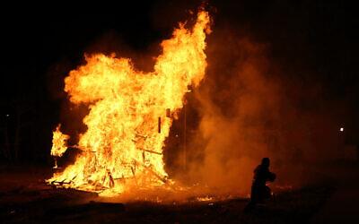 Illustrative image: An ultra-Orthodox Jewish boy runs near a giant bonfire, during celebrations of the Jewish holiday of Lag B'omer in Jerusalem's Mea Shearim neighborhood, April 28, 2013. (Yaakov Naumi/Flash90)