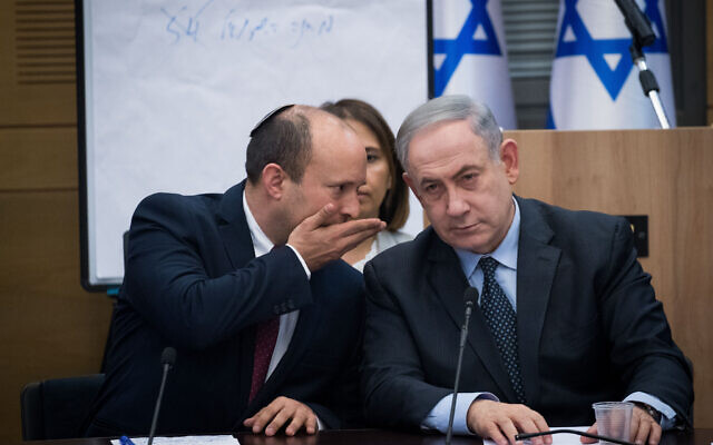 Prime Minister Benjamin Netanyahu, right, speaks with then Defense Minister Yamina party leader Naftali Bennett, March 4, 2020. (Yonatan Sindel/Flash90)