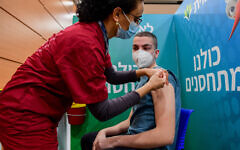 Illustrative: An Israeli student receives a COVID-19 vaccine injection at a Leumit vaccination center in Tel Aviv, on January 23, 2021, just after the country rolled out inoculation to everyone aged 16-plus. (Avshalom Sassoni/Flash90)