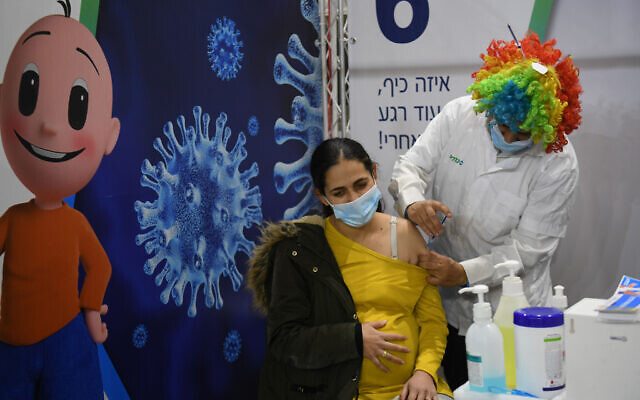 A pregnant woman receives a Covid-19 vaccine injection, at Clalit Covid-19 vaccination center in Or yehuda, on Purim, February 25, 2021. (Flash90)
