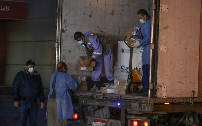 Palestinians from Gaza's health ministry unload boxes of Russian Sputnik V vaccine doses sent by the United Arab Emirates, at the Rafah crossing in the southern Gaza Strip, on March 11, 2021. (Abed Rahim Khatib/Flash90)