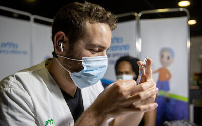 A health worker prepares a COVID-19 vaccine shot at a vaccination center in Jerusalem, on March 11, 2021. (Yonatan Sindel/Flash90)