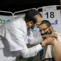 Illustrative image: a Haredi man receives a coronavirus vaccine in Jerusalem, on March 11, 2021. (Yonatan Sindel/Flash90)