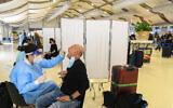 Medical technicians test passengers for COVID-19 at the Ben Gurion International Airport near Tel Aviv on March 8, 2021. (Flash90)