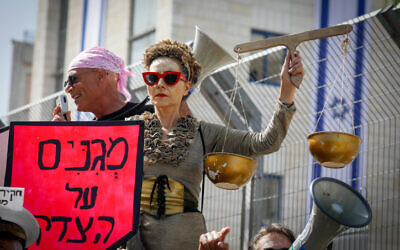 A protester holds symbolic scales of justice outside the District Court in Jerusalem, as Benjamin Netanyahu goes on trial on April 5, 2021. (Olivier Fitoussi/Flash90)