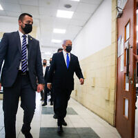 Prime Minister Benjamin Netanyahu arrives for the first session of the evidentiary stage of his trial at Jerusalem District Court on April 5, 2021. He left the hearing after the lead prosecutor's opening statement, before the start of witness testimony, at his own request and with the judges' permission. (Oren Ben Hakoon/POOL)
