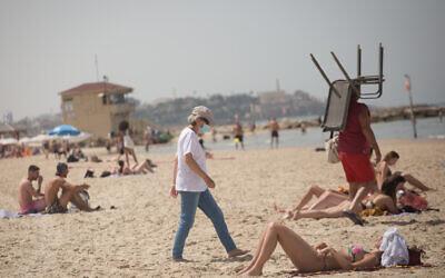 Israelis enjoy the beach on a hot spring day, in Tel Aviv, April 6, 2021.(Miriam Alster/FLASH90)