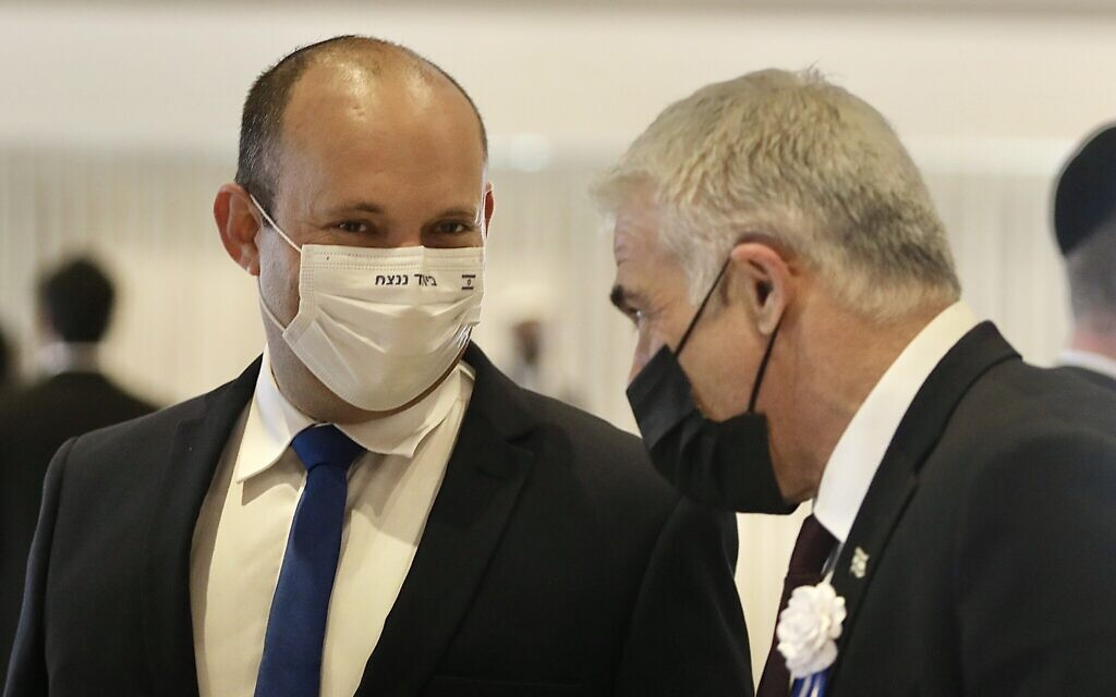 Yamina party leader Naftali Bennett (left) and Yesh Atid leader Yair Lapid during the swearing-in ceremony of the 24th Knesset, at the Knesset building in Jerusalem, April 6, 2021. (Marc Israel Sellem/Pool)