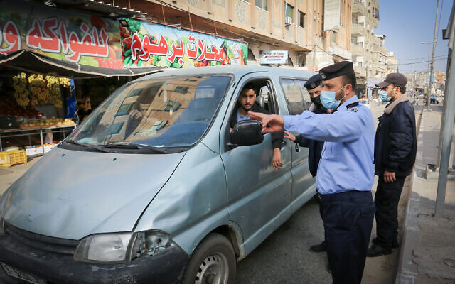 Members of the Palestinian security forces perform checks on the street after a lockdown was ordered in Gaza Strip until April 11, 2021, to curb the spreading of coronavirus. (Abed Rahim Khatib/Flash90