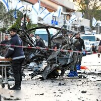 Security forces inspect the scene where a man died in a car explosion in Holon, on April 11, 2021. (Flash90)