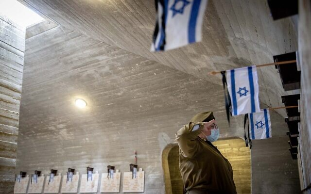 Illustrative: Israeli soldiers place flags on the graves of fallen soldiers in Mount Herzl Military Cemetery in Jerusalem, on April 11, 2021.(Yonatan Sindel/Flash90)