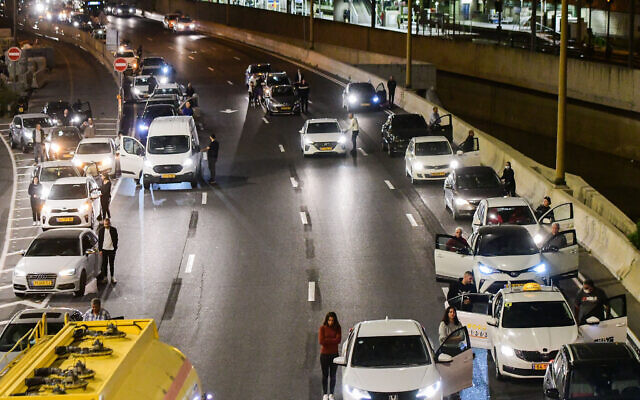 People stand still as one minutre siren sounded across Israel, marking Memorial Day which commemorates the fallen Israeli soldiers and victims of terror in Ayalon highway, Tel Aviv, April 13, 2021. (Avshalom Sassoni/Flash90)