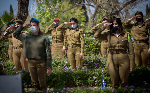 Israeli soldiers lay flowers and Israeli flags on the graves of fallen soldiers at the Kiryat Shaul Military Cemetery on April 13, 2021, ahead of Israeli Memorial Day, which begins tonight. (Miriam Alster/Flash90)