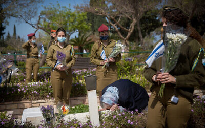 Israeli soldiers lay flowers and Israeli flags on the graves of fallen soldiers at the Kiryat Shaul Military Cemetery on April 13, 2021, ahead of Israeli Memorial Day. (Miriam Alster/Flash90)
