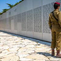 An Israeli soldier looks at a wall with the names of fallen soldiers of the armored corps at Latrun's military memorial, April 13, 2021, ahead of Memorial Day. (Yossi Aloni/Flash90)