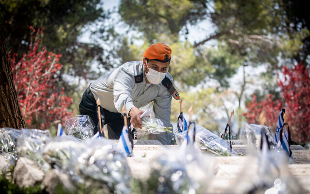Israeli soldiers visit graves of fallen soldiers in Mount Herzl Military Cemetery in Jerusalem, on April 13, 2021, ahead of Israeli Memorial Day, which begins tonight. (Yonatan Sindel/Flash90)